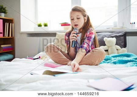 Schoolgirl on bed in her room singing songs with microphone, reading lyrics from book, future musician