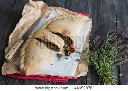 Italian pizza calzone with mushrooms, spinach and cheese on a wooden surface with a bunch of thyme, rustic style selective focus