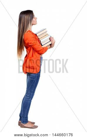 Girl carries a heavy pile of books. back view. girl in a red jacket stands sideways with a stack of books and looking up.