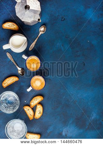 Coffee espresso in cups with italian cantucci, cookies and milk in jug over dark blue painted plywood background, top view, copy space, vertical composition. Food frame concept