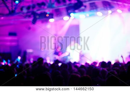 Blurred image of performer on purple-lit stage before large crowd of fans admiring his music