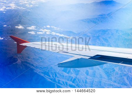Wing of airplane flying above clouds and Caucasus mountains. View of sky from aircraft long distance travel by airtransport. Russian, Krasnodar Krai