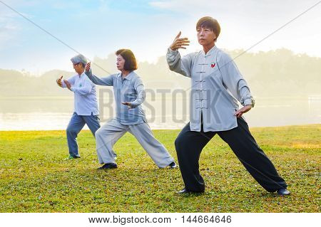 BANGKOK, THAILAND - FEBRUARY 13, 2016: Unidentified group of people practice Tai Chi Chuan in a park.