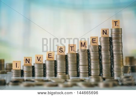 Stack of Coins with Wooden Alphabet Letters