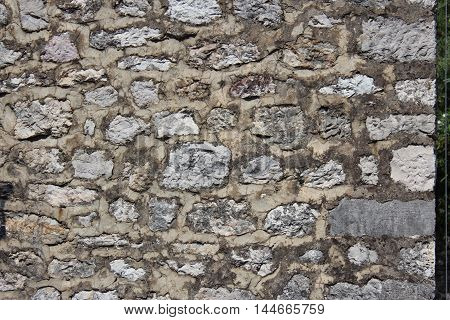 the texture of the wall surface with the rough-hewn stones of varying shapes