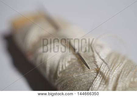 Macro detail of a silver sharp needle inserted in the spool of white thread