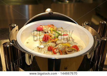 Seafood buffet in stew with tuna bonito mushroom chili and tomatoes in restaurant