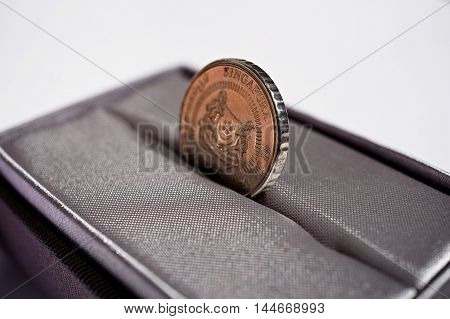 Macro detail of a silver coin of Singaporean currency (Singapore Dollar, SGD) placed in the gray luxurious jewelry gift box as a symbol of luxury and highly appreciated currency of the country of Singapore