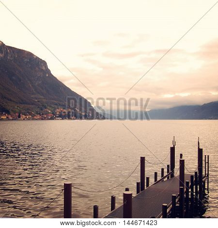 Small pier and calm water. Cloudy day on Como lake. Toned photo. Lake Como near Varenna. Autumn. Walking along the lake Como. Lago di Como Lombardia Italy. Aged image.