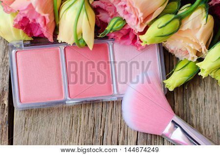 Blush and brush for blush on a wooden table next to the flowers close up. Women's cosmetics