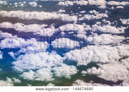 Airplane flying cumulus clouds over Black sea and Caucasus mountains. View of sky from aircraft long distance travel by airtransport. Russia, Krasnodar