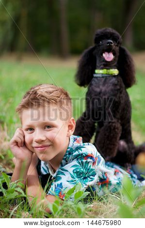 boy with a black poodle lying on green grass