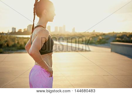 Toned fit young woman standing in her sportswear with her hands on her hips backlit by the sunrise on a rural road taking a break from her workout side view with copy space