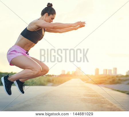Young woman doing crossfit exercises outdoors jumping up onto a low stone wall at the side of a rural road or promenade with raised arms side view with cityscape in the rising sun