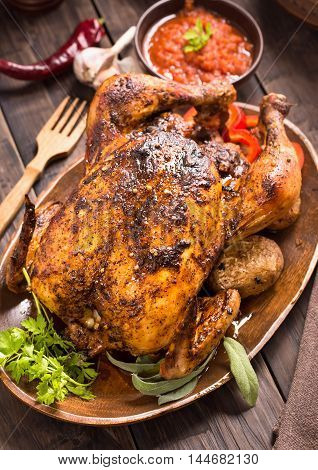 Grilled chicken with vegetables and greens on wooden plate