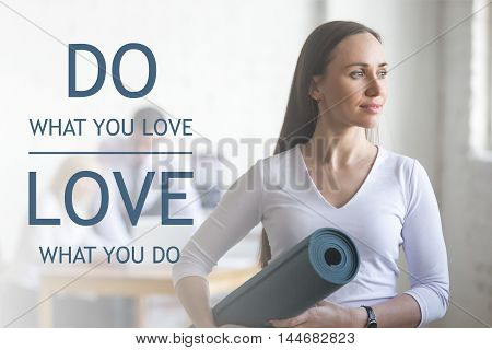 Business and healthy lifestyle concept. Portrait of beautiful sporty young office woman standing with yoga mat at workplace on break time. Motivational text
