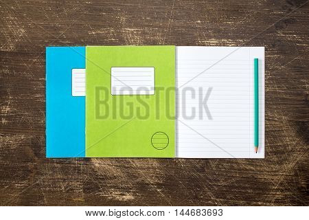 Three exercise books and pencil on the wooden background