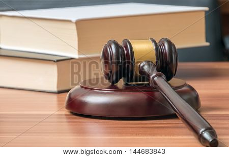 Wooden gavel and books in background. Law and justice concept.