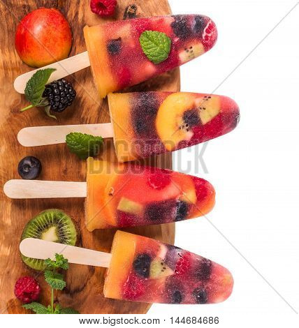 Homemade fresh berry and fruit ice pop top view on white