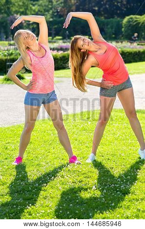 Two Friends In Shorts Practicing Yoga Poses