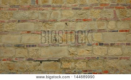 Texture of old wall of red bricks and stones in horizontal format