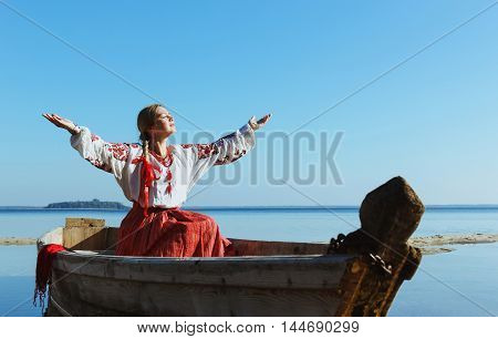 Happy carefree caucasian woman in ukrainian embroidered shirt in boat in glow of sun with arms outspread and face raised in sky enjoying open spaces on lake serenity in nature.