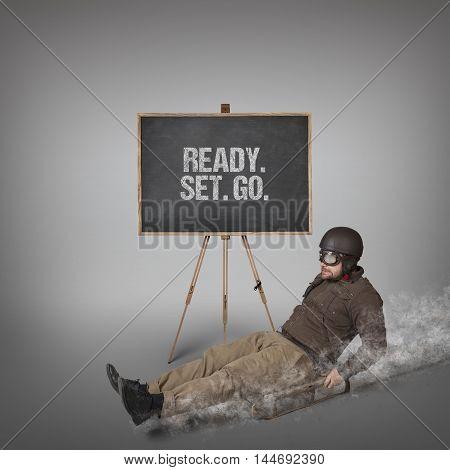 Ready Set Go text on blackboard with businessman sliding with a sledge