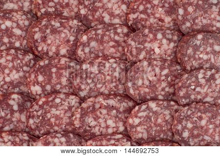 Salami background with many sliced pieces of salami. Top view.
