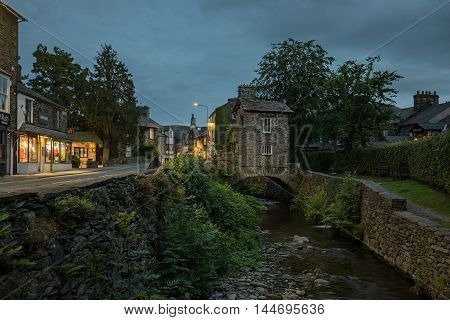 Ambleside, UK July 08, 2016. Bridge House a 17th Century cottage spans Stock Beck on one of the town's main roads. The town is a popular stopping point for tourists exploring the area.