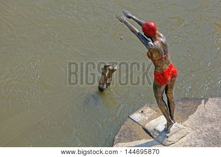 SKOPJE MACEDONIA - SEPTEMBER 17: The Swimmer Statue in Skopje on SEPTEMBER 17 2012. Bronze Sculpture of Diving Swimmer Woman in Bikini at Vardar River in Skopje Macedonia.