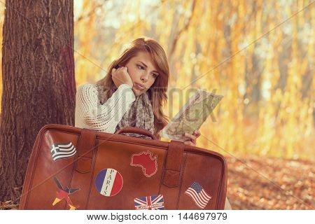 Beautiful young woman sitting on fallen autumn leaves in the park with the suitcase and a map getting ready for a vacation