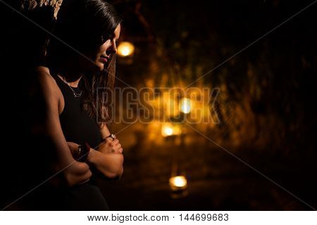 Serious Woman with Crossed Arms in a Garden at Night