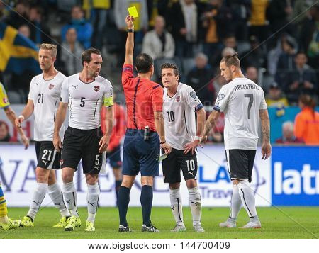 STOCKHOLM, SWEDEN - SEPTEMBER 8, 2015: Carlos Velasco Carballo (Spain) shows the yellow card to Zlatko Junuzovic (Austria) in an European Championship qualification game.