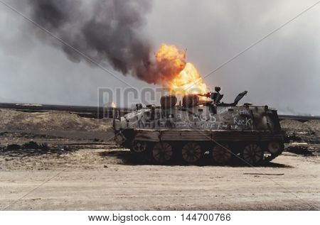 Kuwait City Kuwait - April 1991 : Damaged tank on road with burning oil fire from Persian Gulf War.