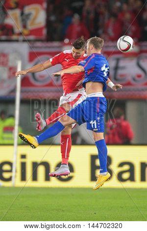 VIENNA, AUSTRIA - SEPTEMBER 5, 2015: Aleksandar Dragovic (Austria) and Nicolae Milinceanu (Moldavia) fight for the ball in an European Championship qualification game.
