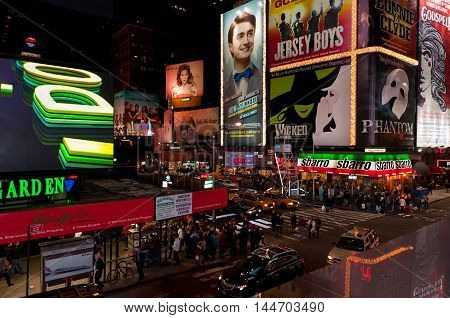New York NY USA - November 20 2011: Night traffic across Times square in New York City. Huge billboards advertising Broadway theater productions adorn the sides of midtown Manhattan buildings at the intersection of 47th Street and 7th Avenue in Times Squa