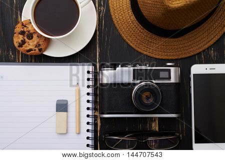Close-up of notepad with pencil and eraser, eyeglasses, phone , hat, camera and a cup of coffee with cookie on dark wooden table