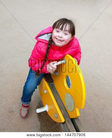 Little girl smiling on the playground .