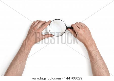 Hands of man holding the magnifying glass isolated on white background. Top view. Optical system. Research and investigation.