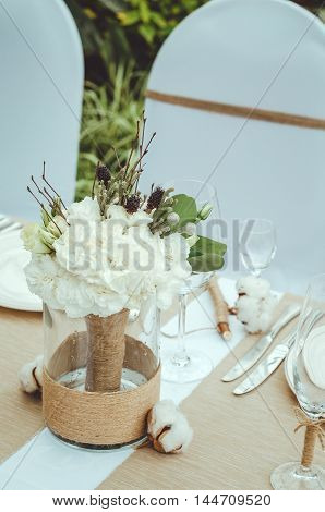 Winter wedding decoration with cotton flower in banquet. Bridal bouquet of white carnations peony roses flowers in vase on table craft background. Lovely nosegay. Winter wedding floral decoration. Twin flower. Text copy space
