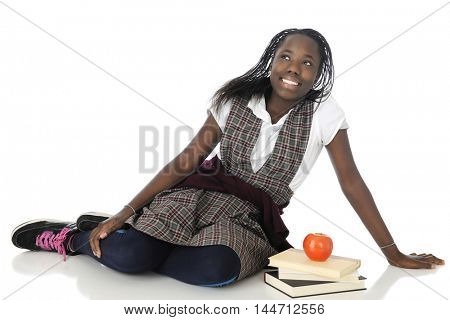 An attractive tween girl happily relaxing in her school uniform, with a small stack of books and an apple beside her.  On a white background.