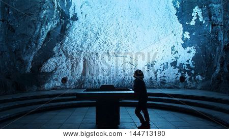 Zipaquira, Cundinamarca / Colombia - January 19 2016: Lonely woman praying in the Salt Cathedral of Zipaquira is an underground Roman Catholic church built within the tunnels of a salt mine