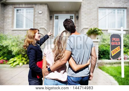 Real Estate agent woman with clients near new house.