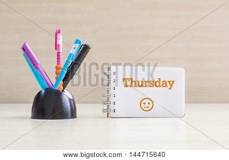 Closeup color pen with black ceramic desk tidy for pen and orange thursday word in white page and normal face emotion at the note book on blurred wood desk and wood wall textured background
