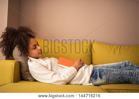 An attractive young woman falling asleep on the couch with a book in hand.
