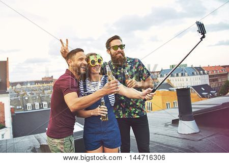 Bearded friend giving rabbit ears to man with beer while woman in sunglasses holds a camera phone at the end of a selfie stick