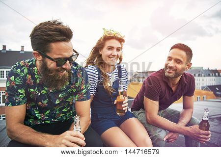 Three happy companions in summer clothing sitting and drinking together on roof in urban setting during summer