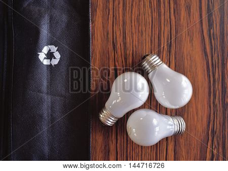 Light bulbs on table mimic recycling triangle