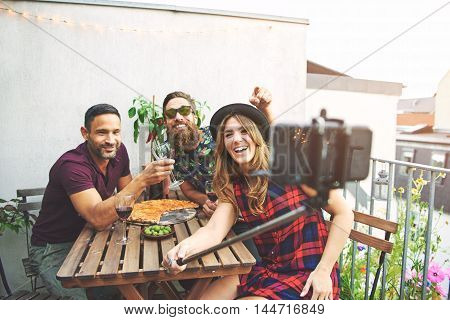 Laughing group of three young adult friends with pizza and wine on table taking selfies