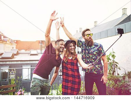 Man with drooping jeans raises one arm and smiles while taking photo with friends who also make arm gestures